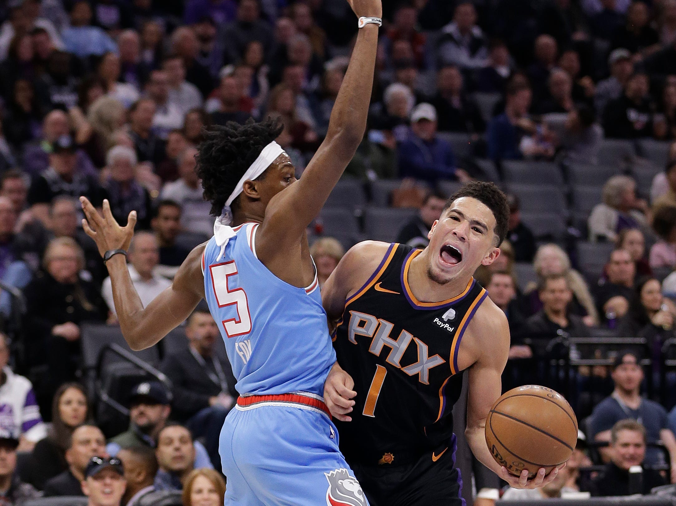Phoenix Suns guard Devin Booker, right, is fouled by Sacramento Kings guard De'Aaron Fox, left, as he drives to the basket against during the first half of an NBA basketball game Sunday, Feb. 10, 2019, in Sacramento, Calif.