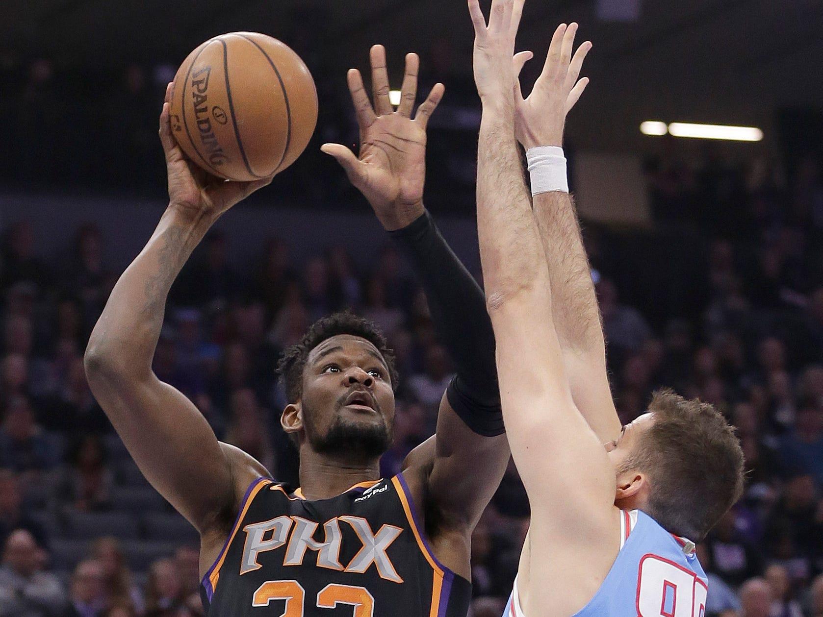 Phoenix Suns center Deandre Ayton, left, shoots over Sacramento Kings guard Bogdan Bogdanovic during the first quarter of an NBA basketball game Sunday, Feb. 10, 2019, in Sacramento, Calif.