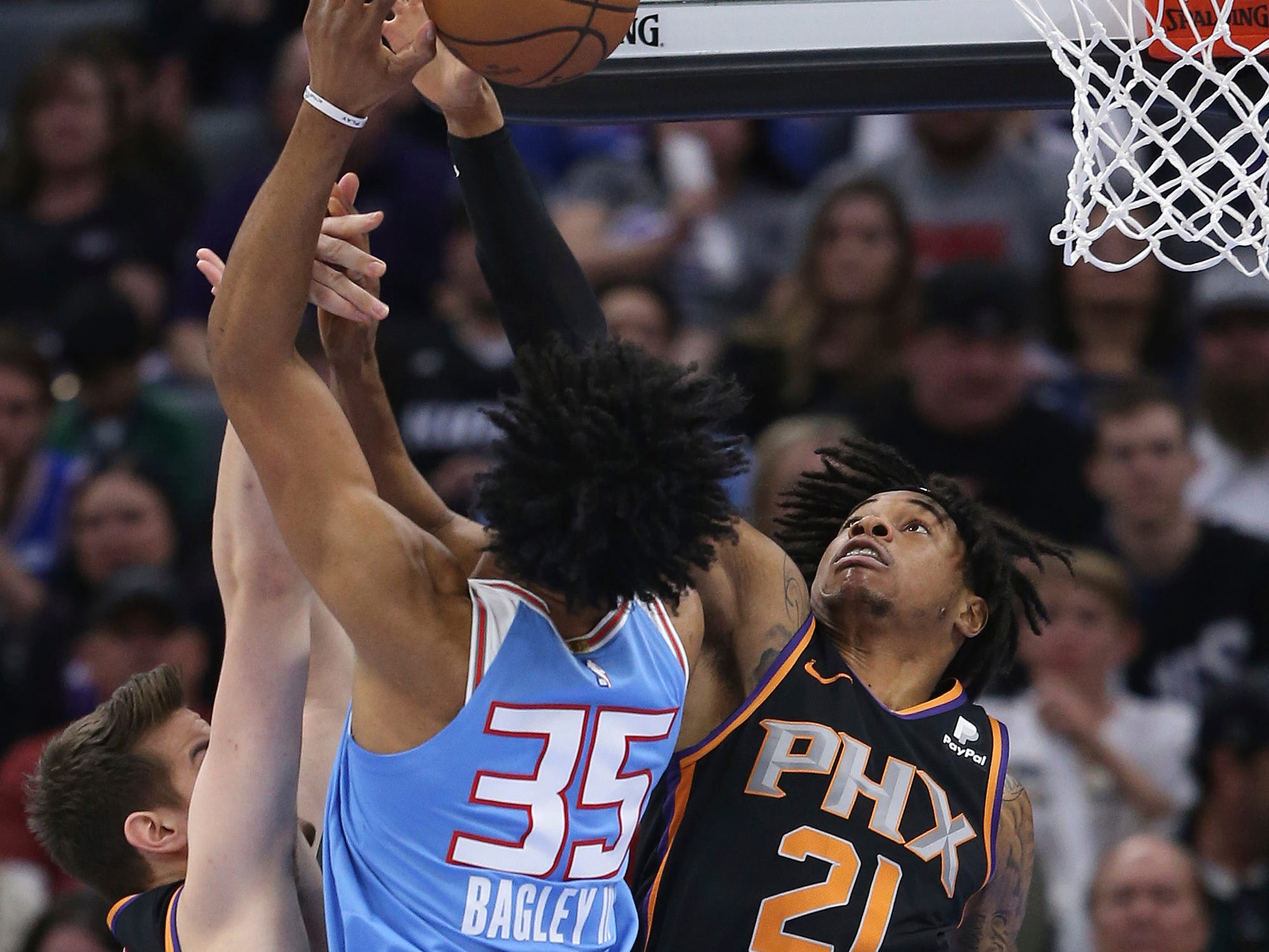 Sacramento Kings forward Marvin Bagley III, left, is fouled by Phoenix Suns forward Richaun Holmes, right, as he goes to the basket during the first half of an NBA basketball game Sunday, Feb. 10, 2019, in Sacramento, Calif.