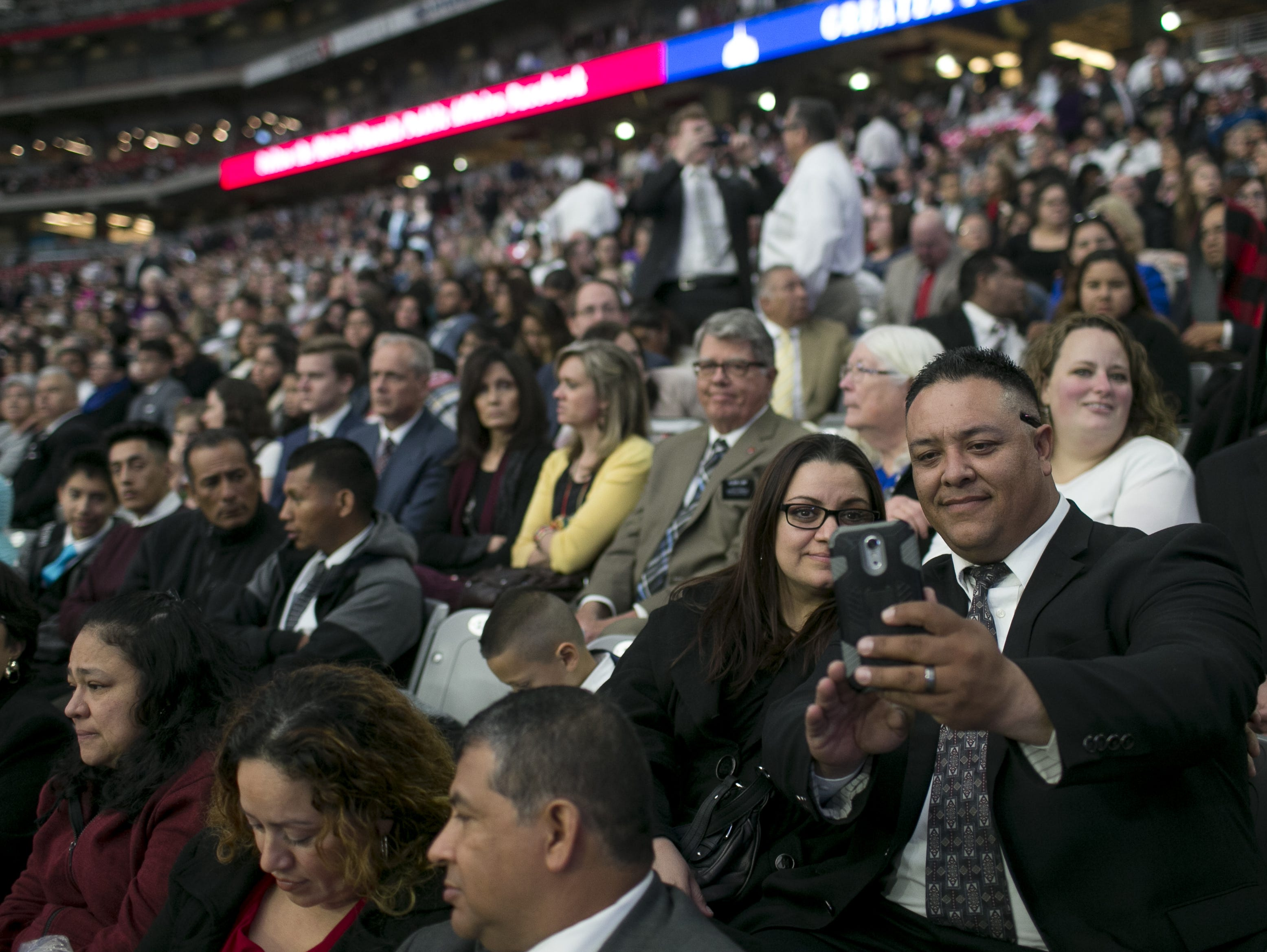 Karla Sanchez (left) and Jesus Sanchez (right) take a selfie while waiting with other members of the Church of Jesus Christ of Latter-day Saints to hear church president Russell Nelson speak at State Farm Stadium in Glendale, Arizona on Sunday, Feb. 10, 2019.