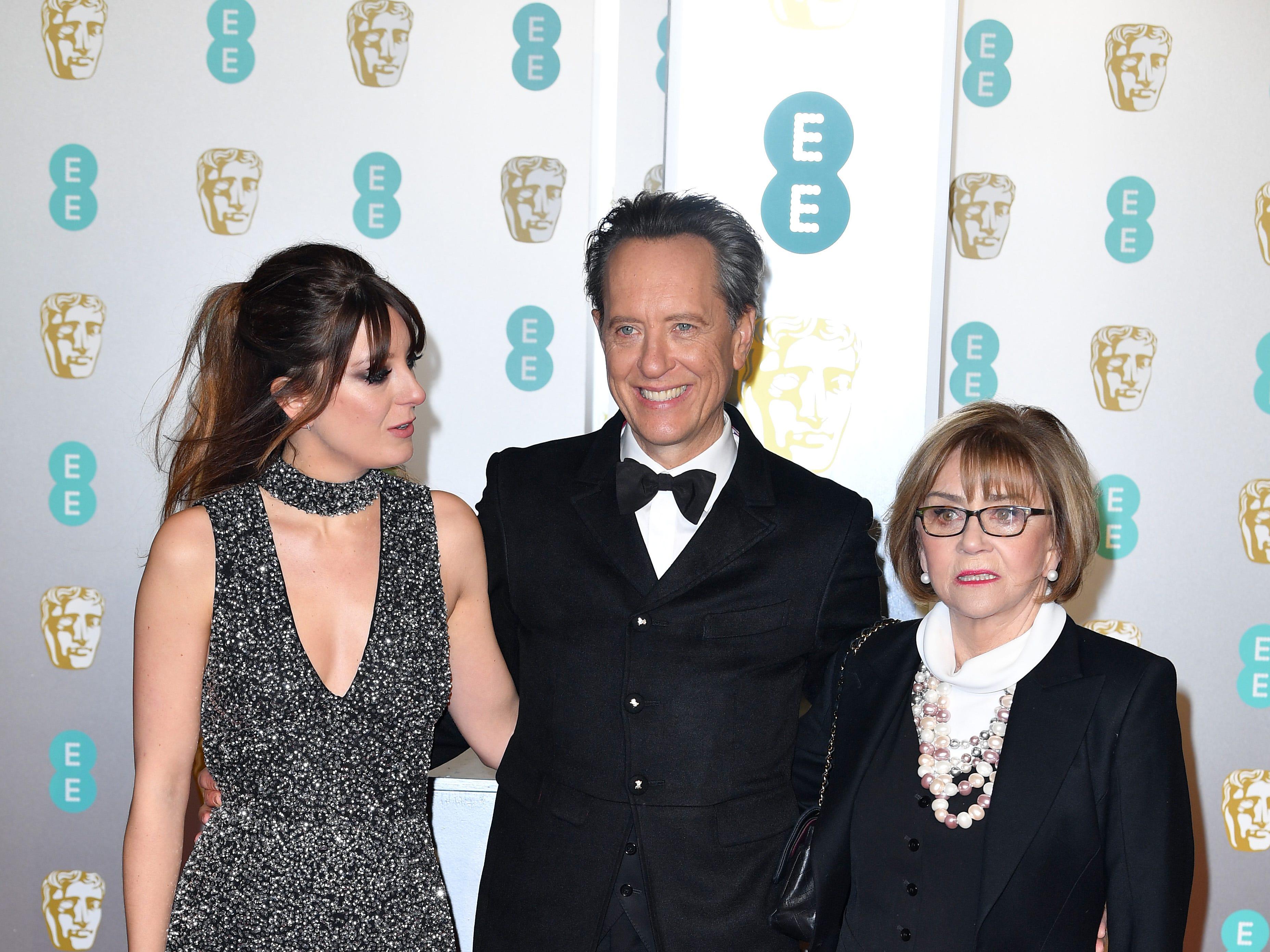Richard E. Grant (centro) y Joan Washington a su llegada a la alfombra roja de los Premios de la Academia Británica de Cine BAFTA en el Royal Albert Hall en Londres el 10 de febrero de 2019.