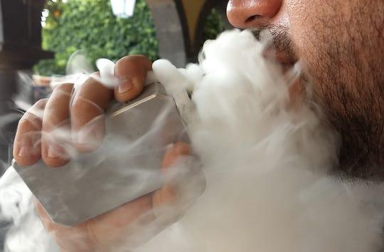 Fotografía del 13 de enero de 2018, de Martín Alonso, de 31 años, fumando un cigarrillo electrónico en una calle de la ciudad de Guadalajara (México).