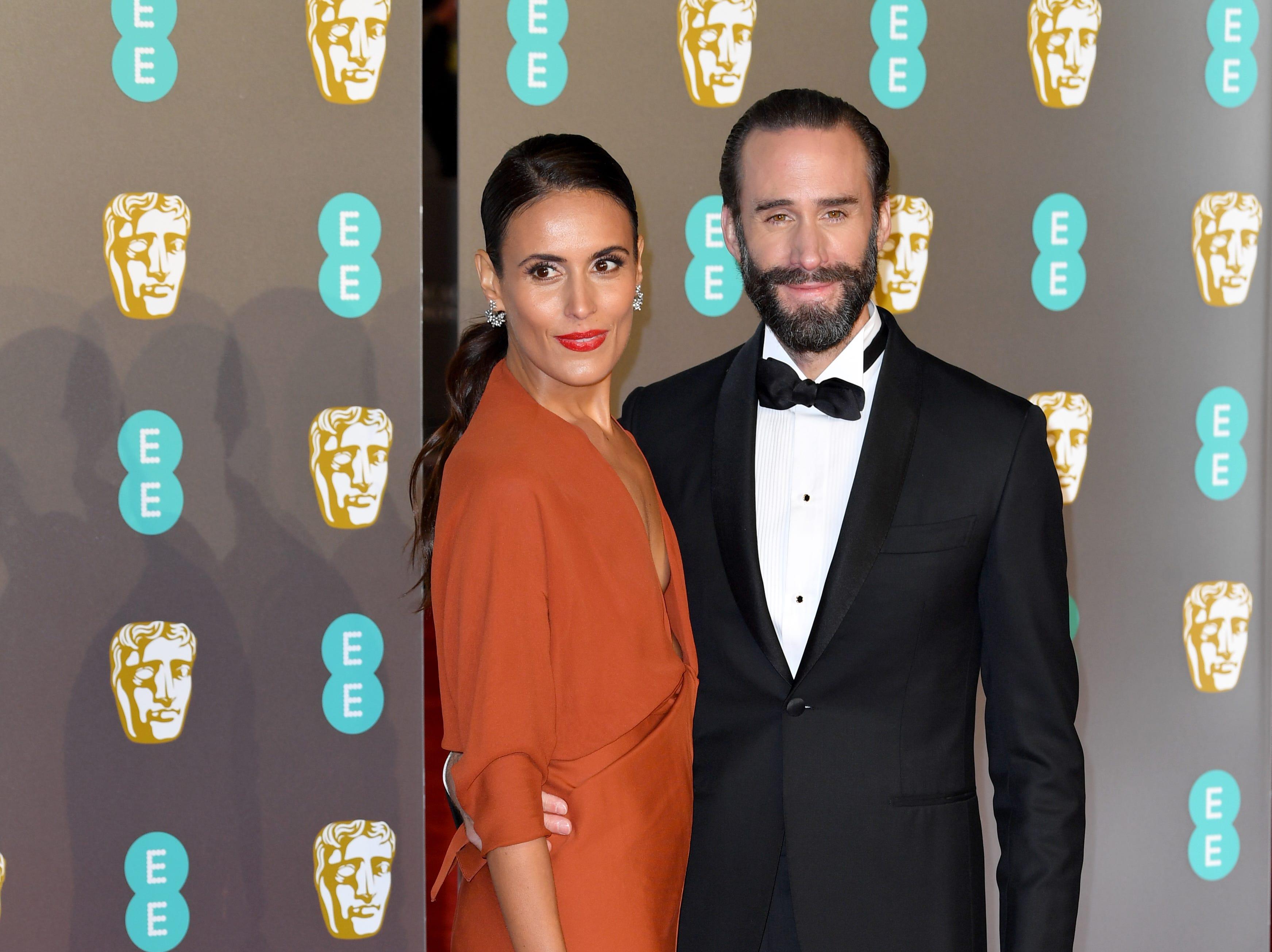 Joseph Fiennes (der) y Maria Dolores Dieguez a su llegada a la alfombra roja de los Premios de la Academia Británica de Cine BAFTA en el Royal Albert Hall en Londres el 10 de febrero de 2019.