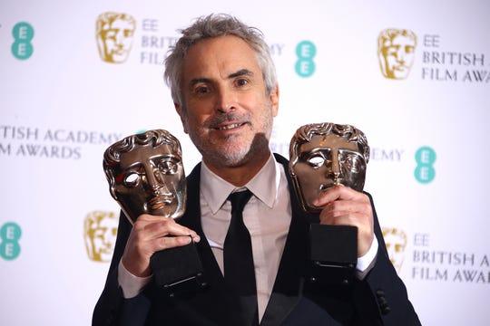 El director Alfonso Cuarón posa con sus dos premios como Mejor Película y Mejor director por 'Roma' en los premios BAFTA en Londres, el domingo 10 de febrero de 2019.