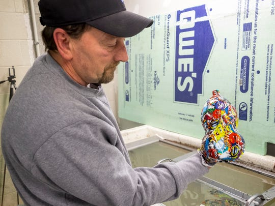 James Stipp, owner of Exceptional Coatings, LLC, holds a plastic speed shape after applying a hydrographic to it Monday, Feb. 11, 2019 in his shop in Port Huron Township.