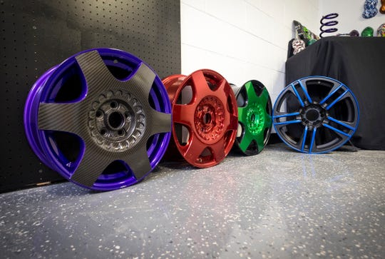 Powder coated wheels are on display at Exceptional Coatings, LLC in Port Huron Township. The wheel on the far left includes a mixed approach of purple powder coating combined with the carbon fiber pattern applied through hydrographics.