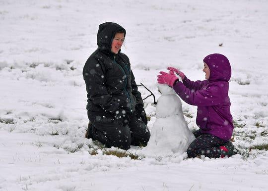 Katrina Patton, left, and daughter Jordan, 12, of Springettsbury Township, build a snowman at Springettsbury Park, Monday, Feb. 11, 2019. John A. Pavoncello photo