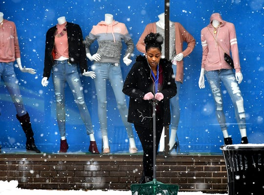 Rainbow Shops Junior Manager Adrianna Fritz shovels snow outside the store's spring fashion window display on West Market Street in York City Monday, Feb. 11, 2019. Forecasters say a mix of sleet, snow and rain is on tap for the area into Tuesday. Bill Kalina photo
