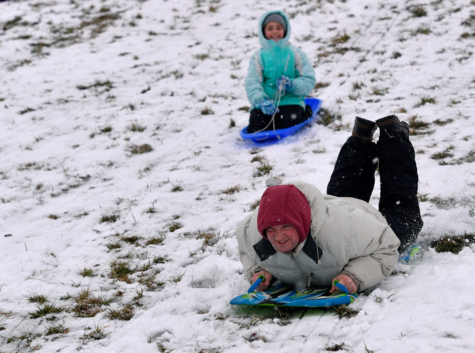Jason Shiffer, right, and daughter Katelyn, 9, of Springettsbury Township, race down the hill while sledding on a snow day at Springettsbury Park, Monday, Feb. 11, 2019. John A. Pavoncello photo