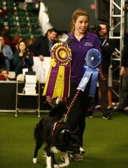 "Perry DeWitt stands with her border collie ""Verb"" after winning the overall competition in the masters agility championship during the Westminster Kennel Club Dog Show, Saturday, Feb. 9, 2019, in New York."