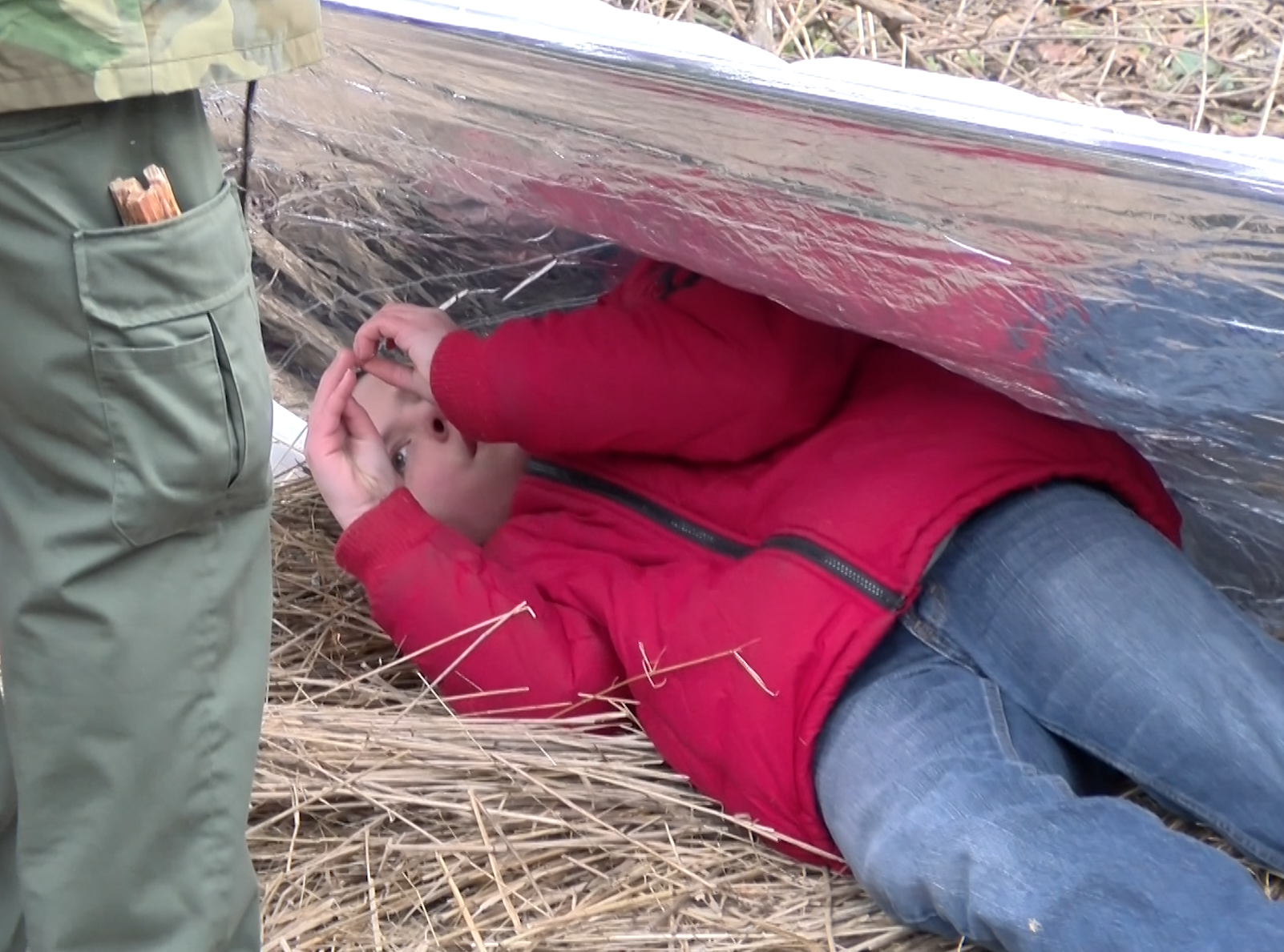 A boy tries out the overnight shelter made during a woodland survival class at the Pa. Game Commission site.