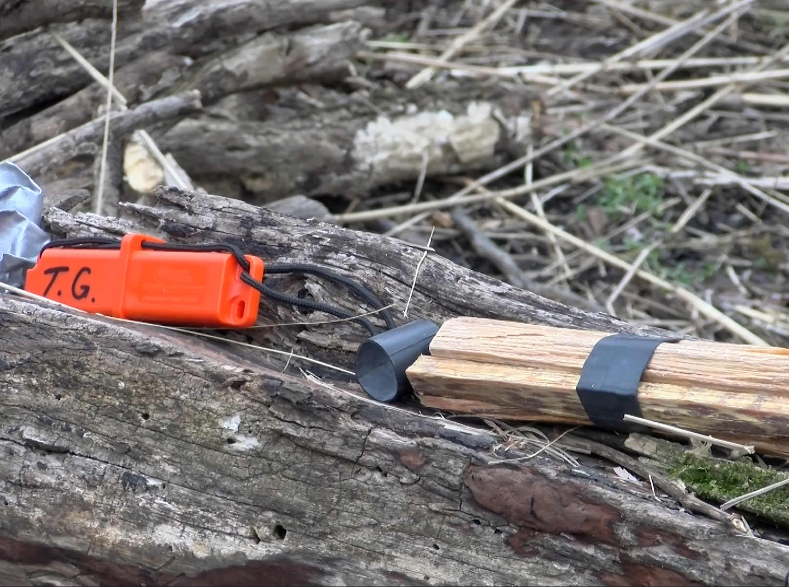 A number of simple fire starting items are displayed on a log during a woodland survival class.