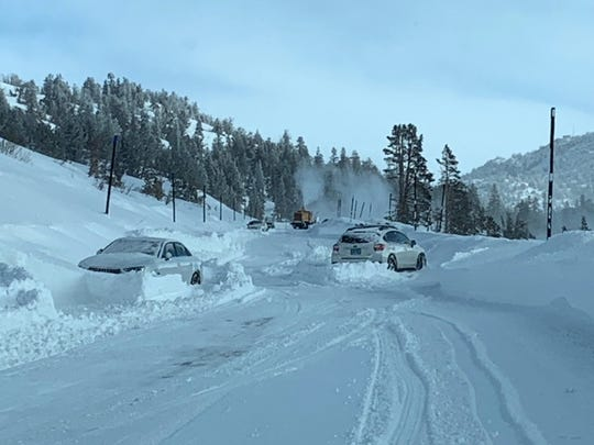 A snowblower cuts a winding path through multiple vehicles trapped in snow in the Sheep's Flat area of the Mt. Rose Highway on Sunday, Feb. 10.