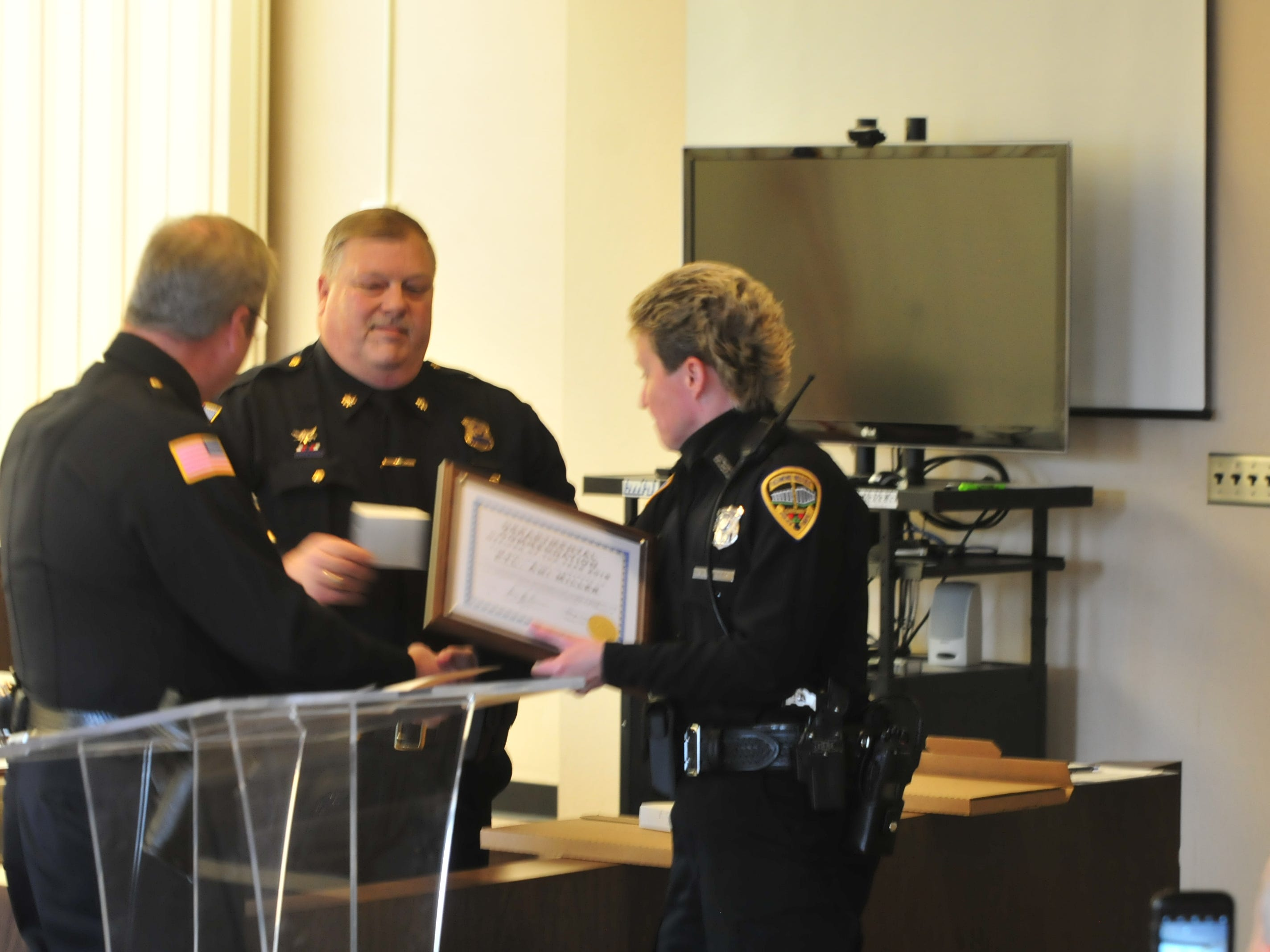 Officer Ami Miller receives her award as Officer of the Year from Chief Jim Branum and Major Mike Britt on Monday.