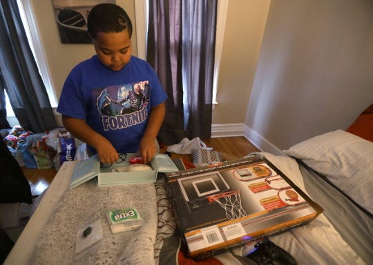 Christian Mason, 11, who was very close with his uncle, Alejandro Ortiz, 18, shows a memory box of things to remind him of his uncle.  He is holding Alejandro's glasses.  Inside is a lock of his uncle's hair, some stones with messages and gum.  Alejandro died Saturday at the Isaiah House.