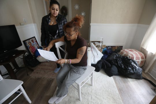 Evelice Ortiz looks over her lease with her cousin, Nelinda Gonzalez behind her.  Around them are donations people gave to Ortiz after hearing about her and her son's homelessness struggle while also taking care of her 18-year-old brother who's heart was failing.