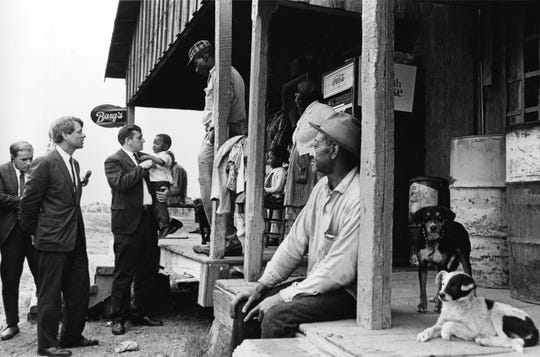 Sen. Robert F. Kennedy, D-N.Y., left, talks with a group of people in front of a country store during his tour of the Mississippi Delta near Greenville, Miss., on April 11, 1967. Kenneth Dean of the Mississippi Council of Human Relations, who is holding a child suffering from a diet deficiency. Kennedy is visiting the area with three other senators investigating the federal antipoverty program.