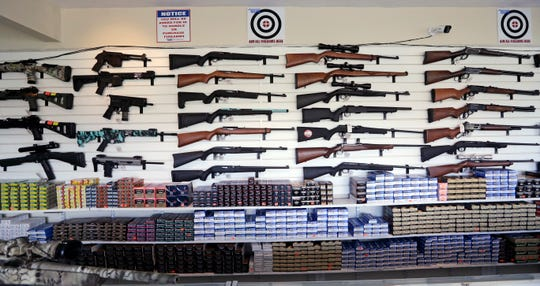 Rifles and ammunition line a wall at a gun shop in Lynnwood, Wash. Voters in Washington state will decide the fate of Initiative 1639, which seeks to curb gun violence by toughening background checks for people buying semi-automatic rifles, increasing the age limit to 21 for buyers of those guns and requiring safe storage of all firearms.