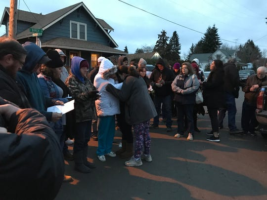 "Family and friends huddle as they sing ""Amazing Grace"" to honor 2-year-old Christopher James Pearce who died in a suspected arson house fire Feb. 1."