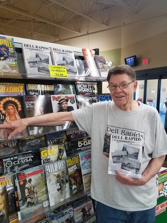 Craig Kumerfield stands in front of the book rack at County Fair in Dell Rapids with his new book, 'Dell Rapids, A Walk Through History.'
