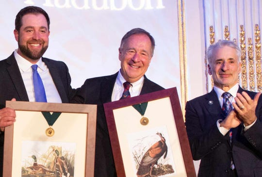 Johnny Morris (center) accepts the Medal with son John Paul from National Audubon Society CEO David Yarnold (right).