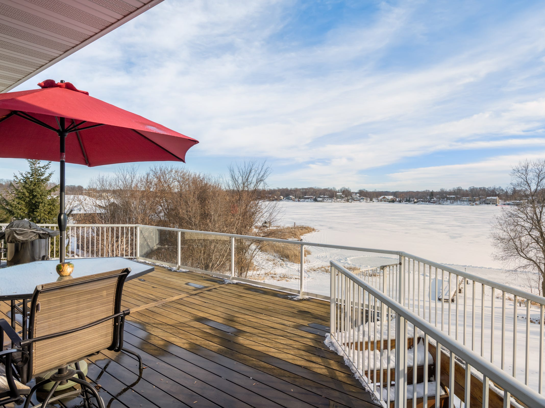 This walkout home has a Tigerwood deck with a glass railing.