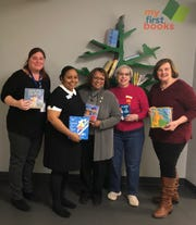 From left, ELC staff Melanie Worley and Lizbeth Murphy welcome the delivery of books by DKG members Monica Hayes, Rhonda Work and Nancy Watson.