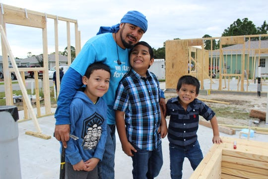 Edgar, a Habitat for Humanity home buyer, standing on the site where construction of his family's future home began in December. Also pictured are Edgar's two sons, Edgar Jr., 10, and Daniel, 6. Edgar's nephew Aurelio Cortez joined the family to celebrate the Habitat Home Wall Raising Ceremony.