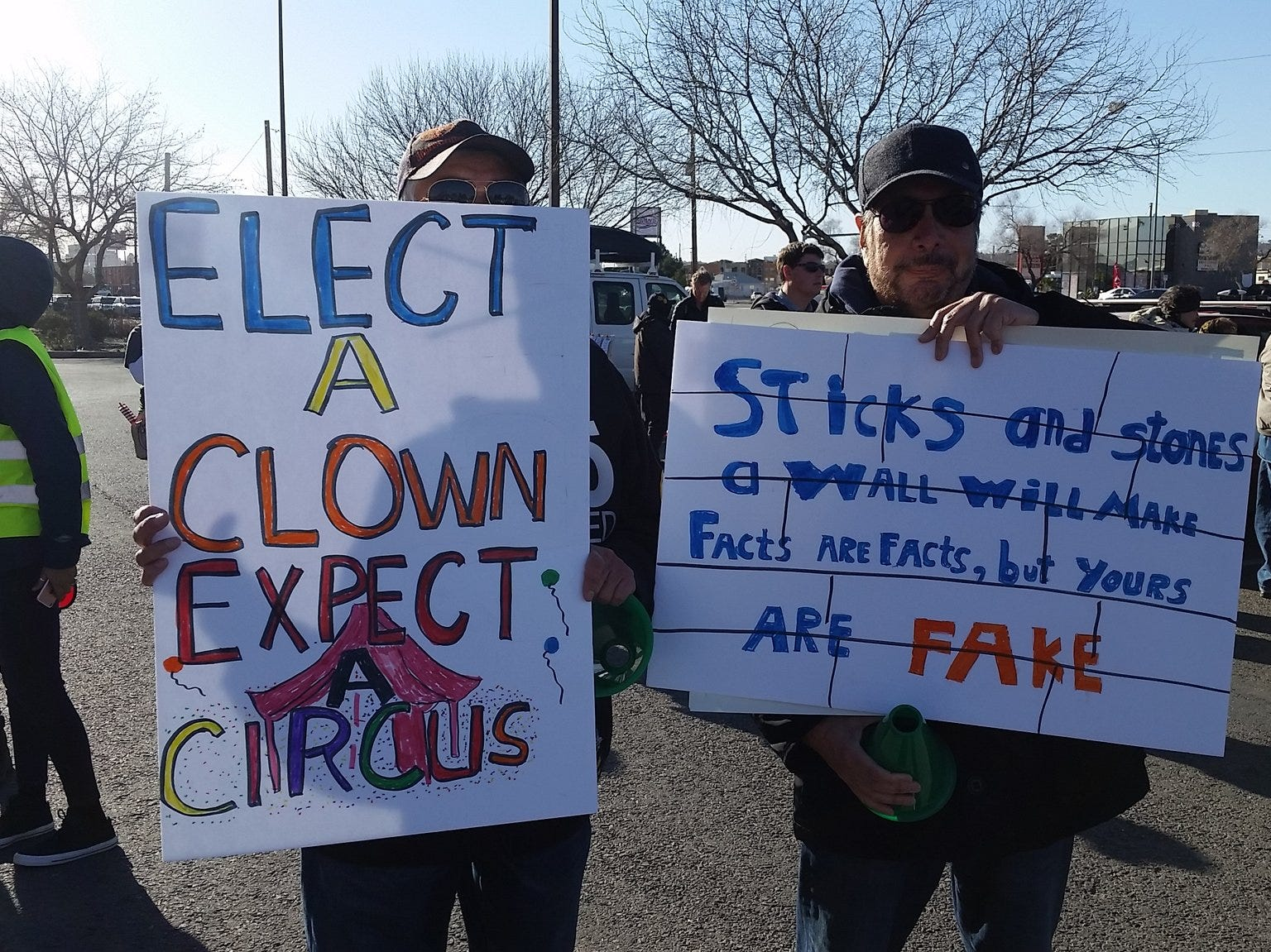 Rafael Hernandez, left, and Tony Murillo, both of El Paso, hold signs protesting President Donald Trump. Both say they were upset at Trump's remarks about El Paso in the State of the Union speech and want to send a different message Monday.