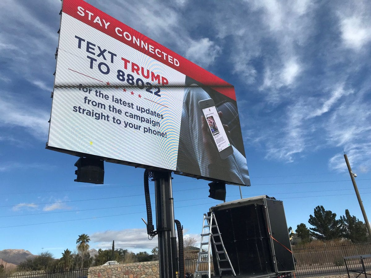 A sign urges people to get the latest updates on President Donald Trump's campaign via text service.