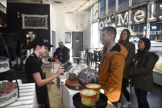 Claire Stevens helps customer Mike Morales place an order on Monday at Rou-Meli, an order at the counter eatery in Oxnard.