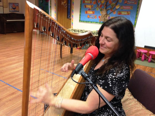 Lori Sunshine, of Ventura, a music therapist, plays the harp during a valentine's box social at Unitarian Universalist Church in Ventura.
