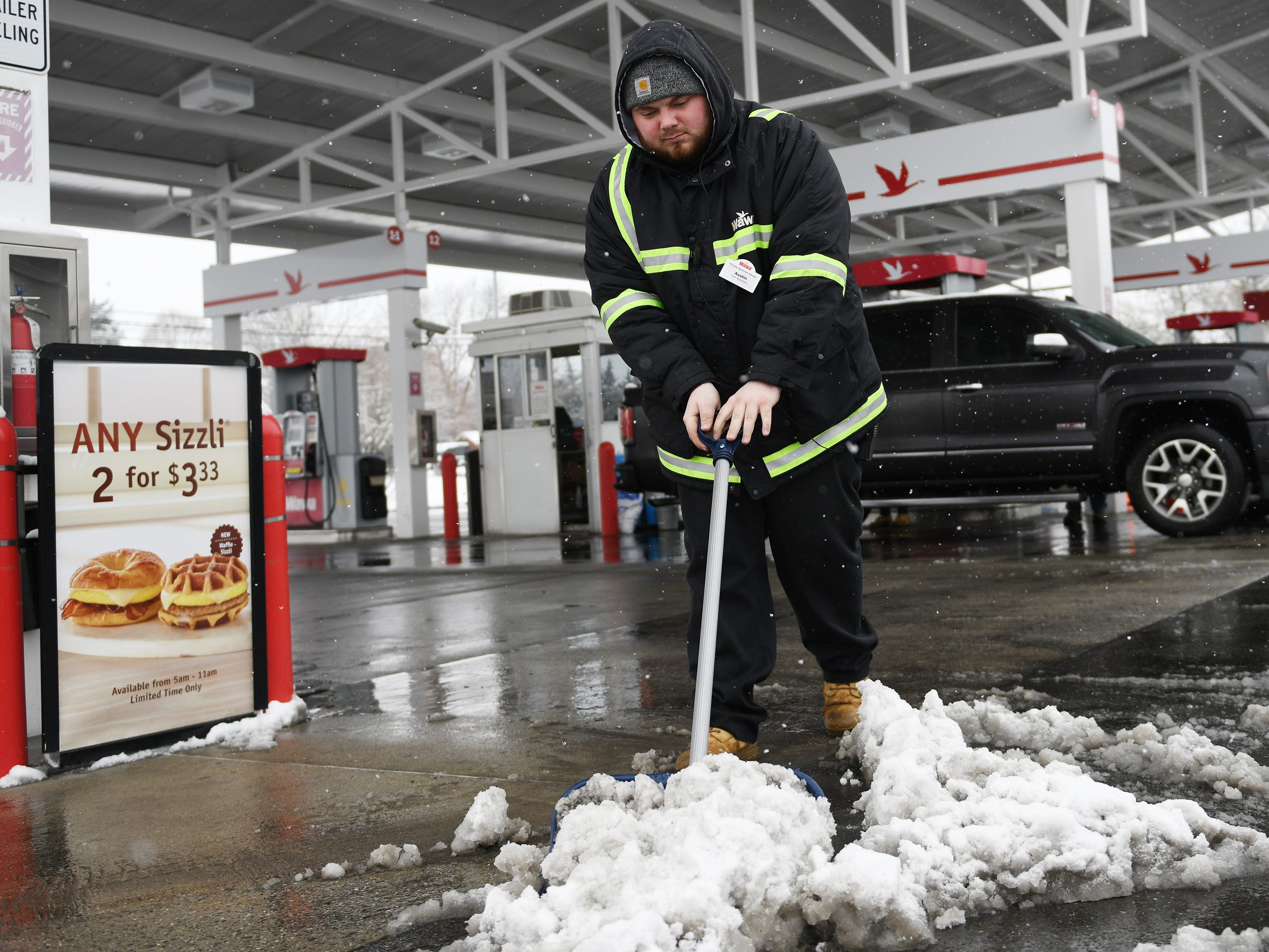 Wawa gas attendant Austin Forvour, 21, of Mays Landing, shovels snow at the Buena location on Monday, Feb. 11, 2019.