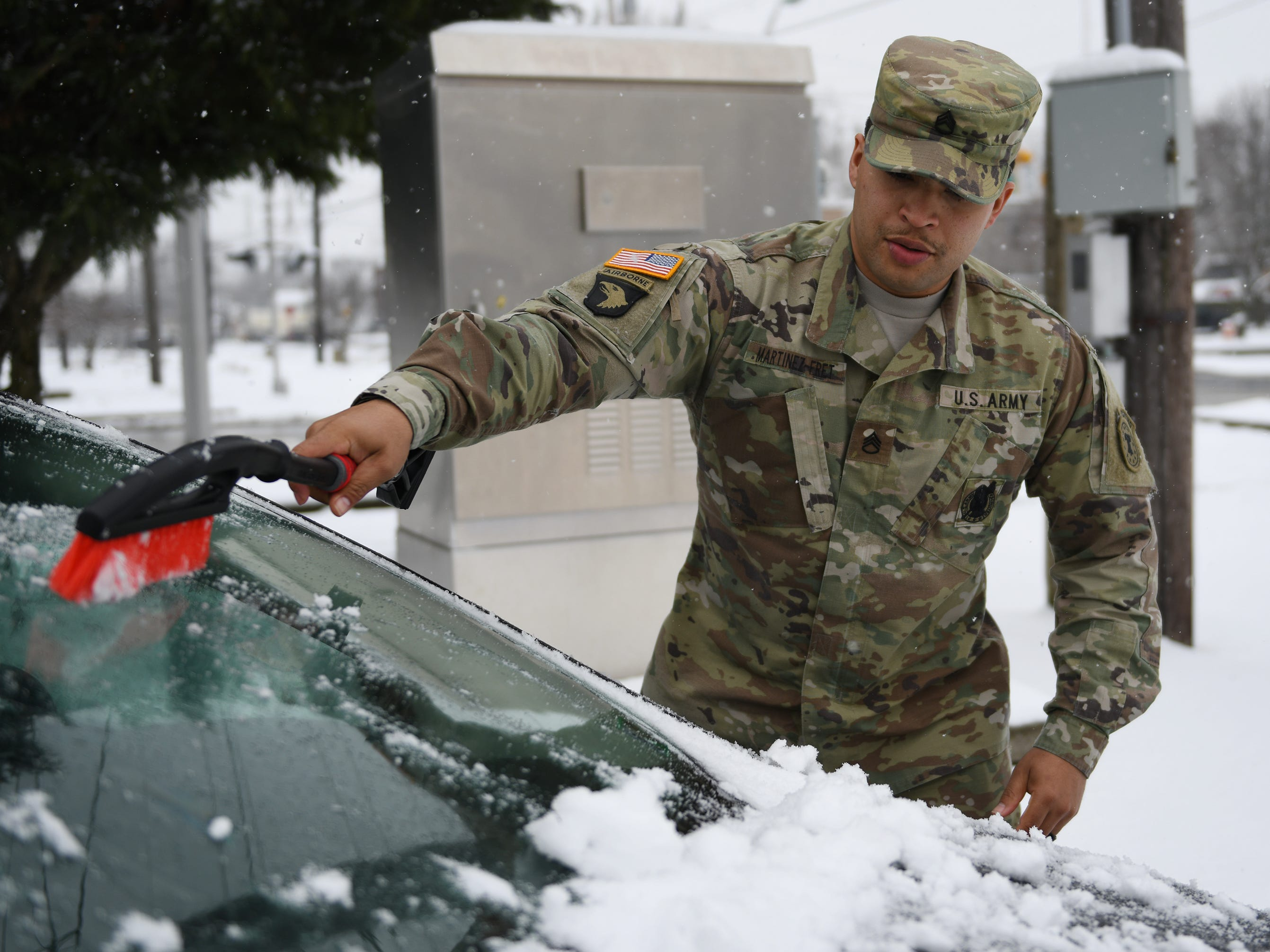 U.S. Army Recruiter Jay Martinez brushes snow of his car in Vineland on Monday, Feb. 11, 2019.