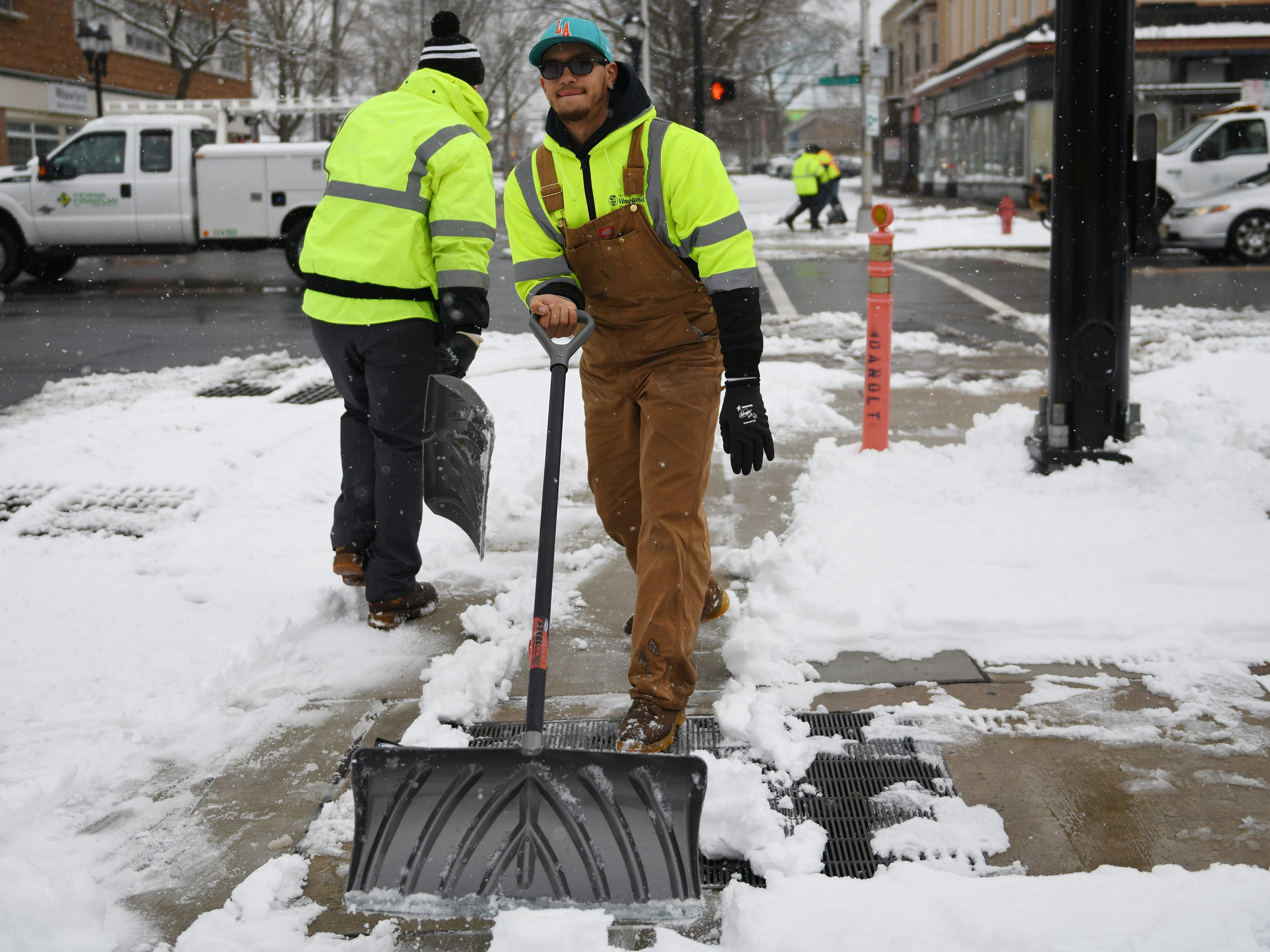 City of Vineland Public Works employees shovel snow from crosswalks on Landis Avenue on Monday, Feb. 11, 2019.