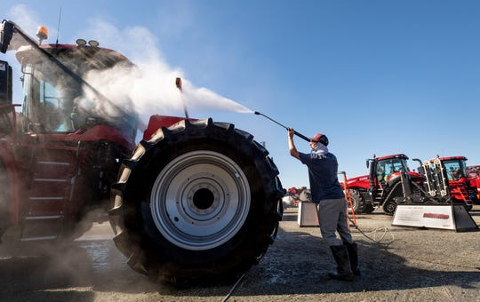 Sam Carnes pressure washes a Case 470 Steiger in preparation for the World Ag Expo at the International Agri-Center in Tulare on Monday, February 11, 2019.