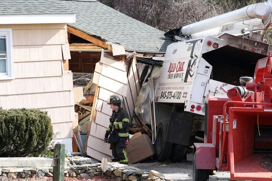Putnam Lake firefighters work at the scene of a crash in which an unoccupied tree service truck rolled down a hill and crashed into a house in Putnam Lake Feb. 10,  2019. There were no injuries to the residents, but the house suffered considerable structural damage.