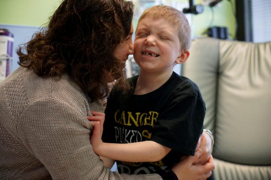 Erica Avello givers her 7 year-old Frankie Knowles, who is undergoing chemotherapy at Nemour/A.I duPont Hospital for Children, a kiss while waiting to start a weekly treatment to treat his tumor the size of a walnut deep within his brain, and four smaller tumors on his spine.