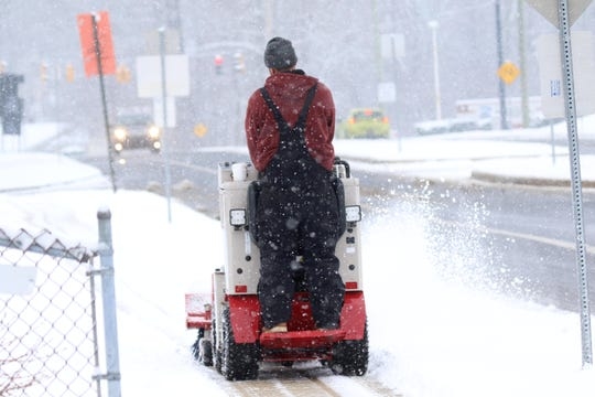 A maintenance workers clear snow from sidewalks along Faulkland Rd. during Delaware's most recent snowstorm.