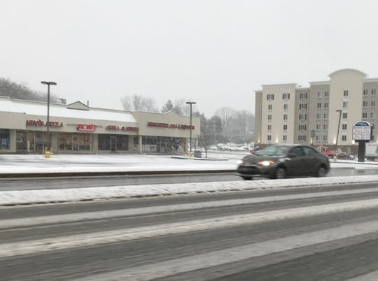 Cars maneuver through slush on South College Drive in Newark on Monday.