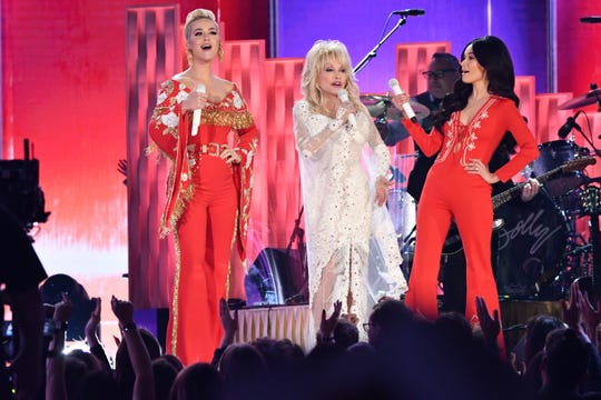 "Katy Perry, left, and Kacey Musgraves, right, flank Dolly Parton to sing ""Here You Come Again"" as part of a tribute to the country icon."