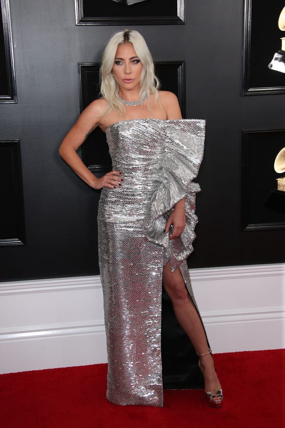Lady Gaga in in a strapless Celine by Hedi Slimane metallic dress with a sculpted accent and high slit at the 2019 Grammy Awards.