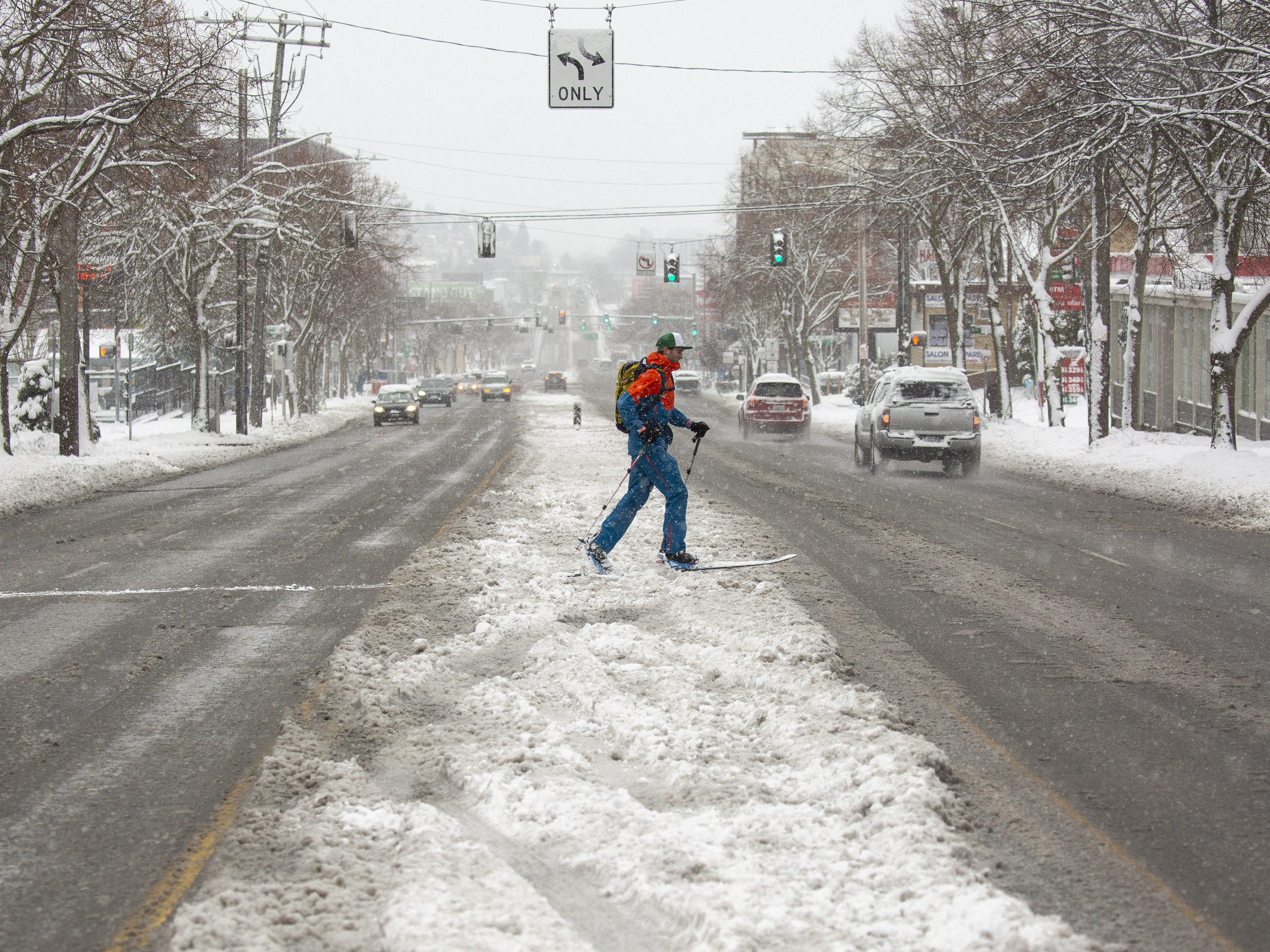 A man crosses a road on skis in the Ballard neighborhood after a large storm blanketed the city with snow on February 9, 2019 in Seattle, Washington.