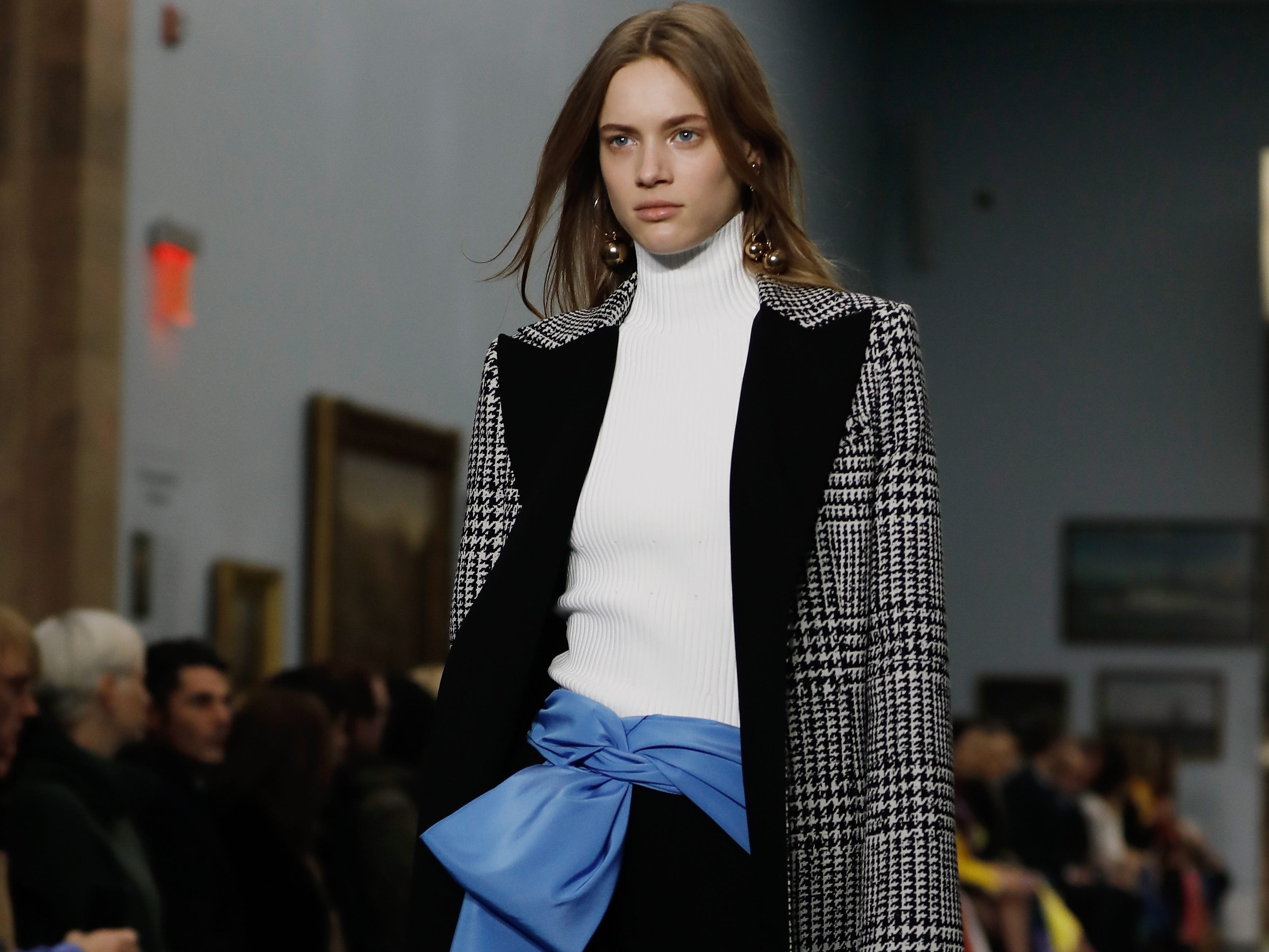 Herrera's use of color was more subtle in this look. A cornflower-blue silk bow broke up a white turtleneck and black trousers worn under a houndstooth coat with black lapels.