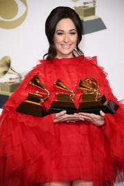 "Kacey Musgraves poses with her awards for best country album and album of the year for ""Golden Hour,"" best country song for ""Space Cowboy"" and best country solo performance for ""Butterflies."""