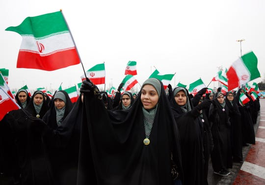 Female students wave Iranian national flags during a ceremony marking the 40th anniversary of the 1979 Islamic Revolution, in Tehran, on Feb. 11, 2019.