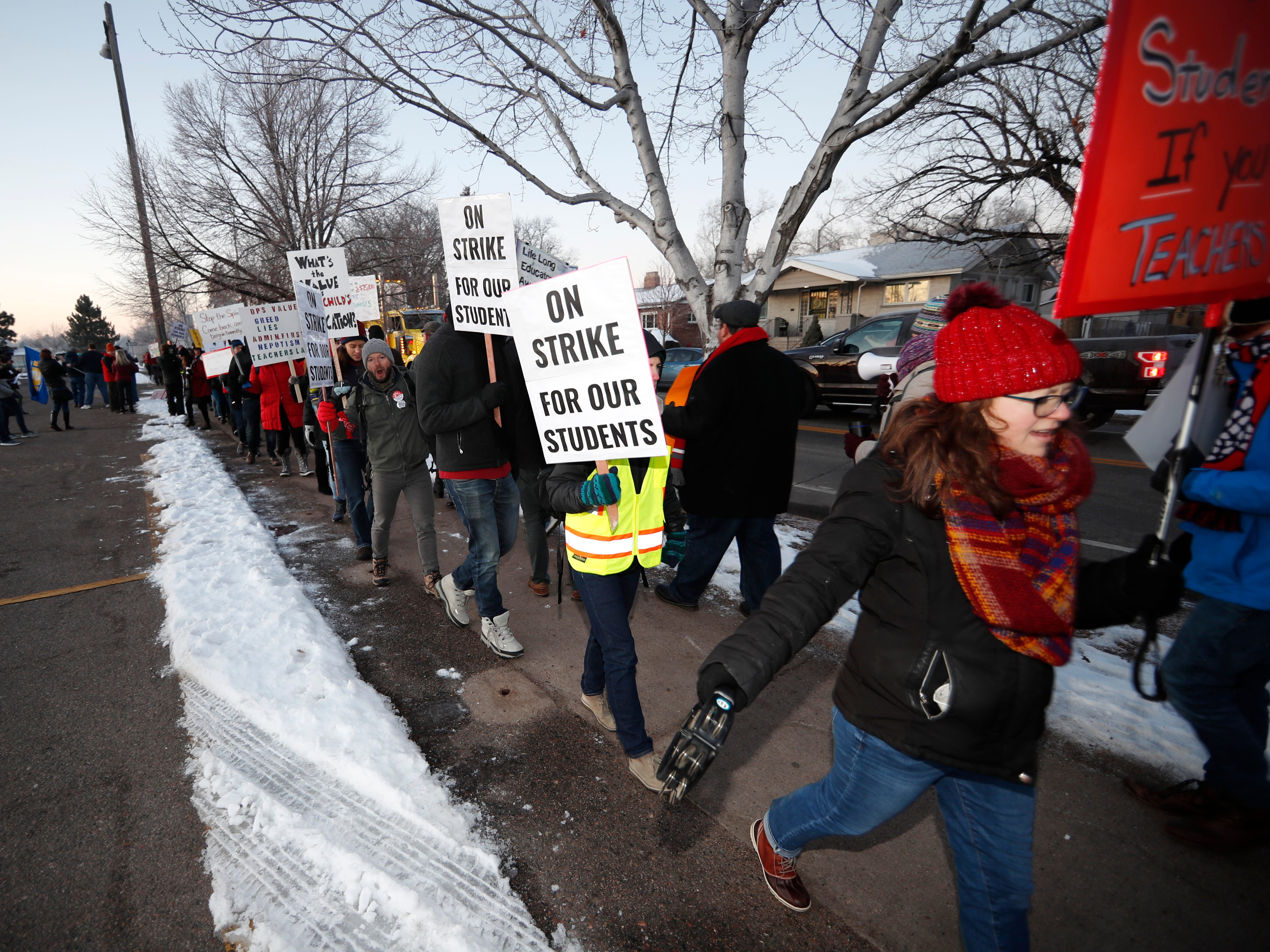 Teachers carry placards as they walk a picket line outside South High School early Monday, Feb. 11, 2019, in Denver. The strike on Monday is the first for teachers in Colorado in 25 years after failed negotiations with the school district over base pay. (AP Photo/David Zalubowski) ORG XMIT: CODZ110