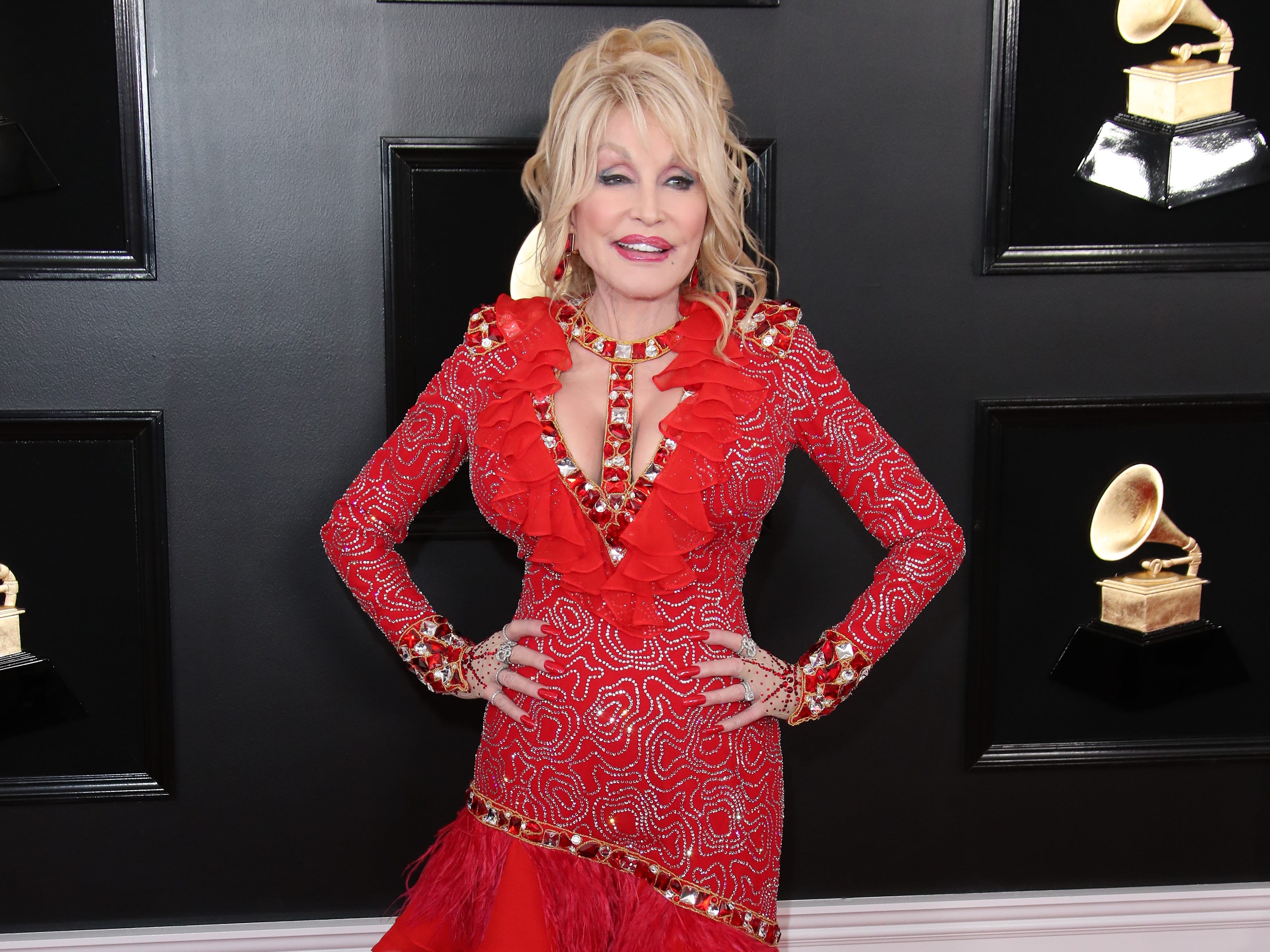 Dolly Parton, matching the Grammys carpet in bright red, lead the crowd in a Dolly sing-along.