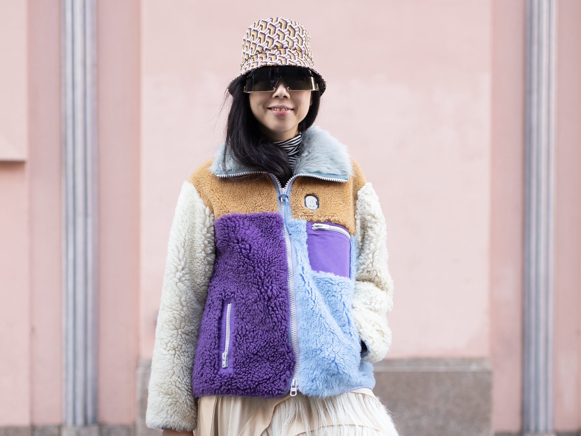 Susie Lau is seen on the street during New York Fashion Week AW19 wearing fleece jacket with fringe skirt and Prada bucket hat on February 10, 2019 in New York City.