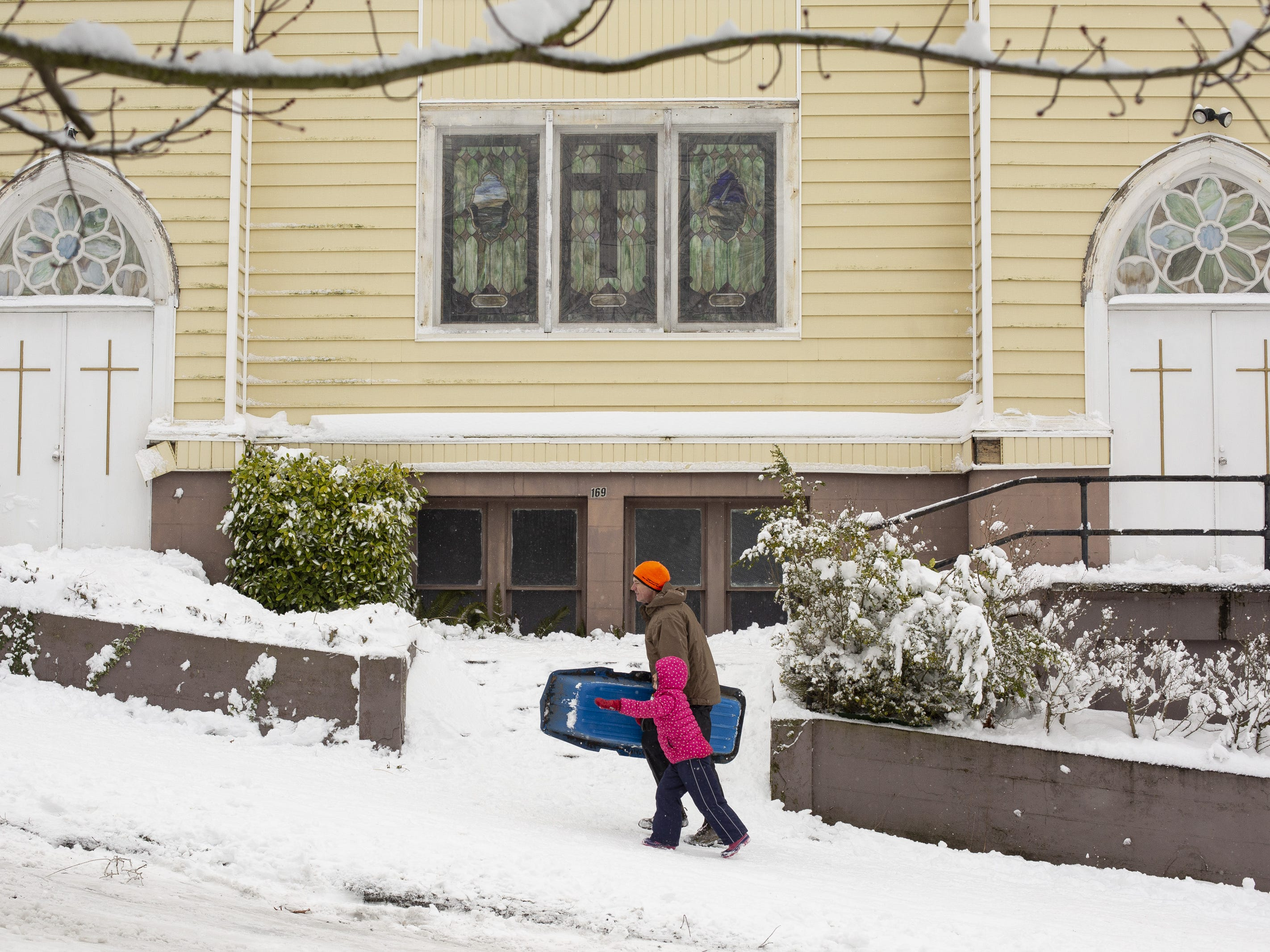 People walk up a hill to go sledding in the Phinney Ridge neighborhood after a large storm blanketed the city with snow on February 9, 2019 in Seattle, Washington.